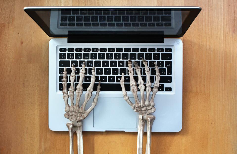 Skeleton hands typing in laptop
