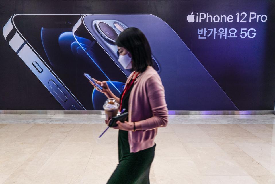A woman wearing a mask walks past an iPhone 12 advertisement...