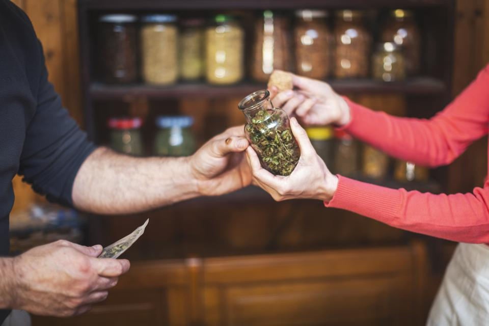 Adult man buys cannabis buds at small cannabis store.