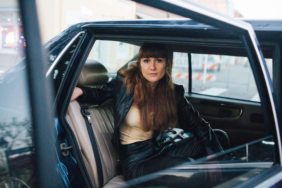 A white woman with brown hair and bangs sits in the backseat of a classic car.