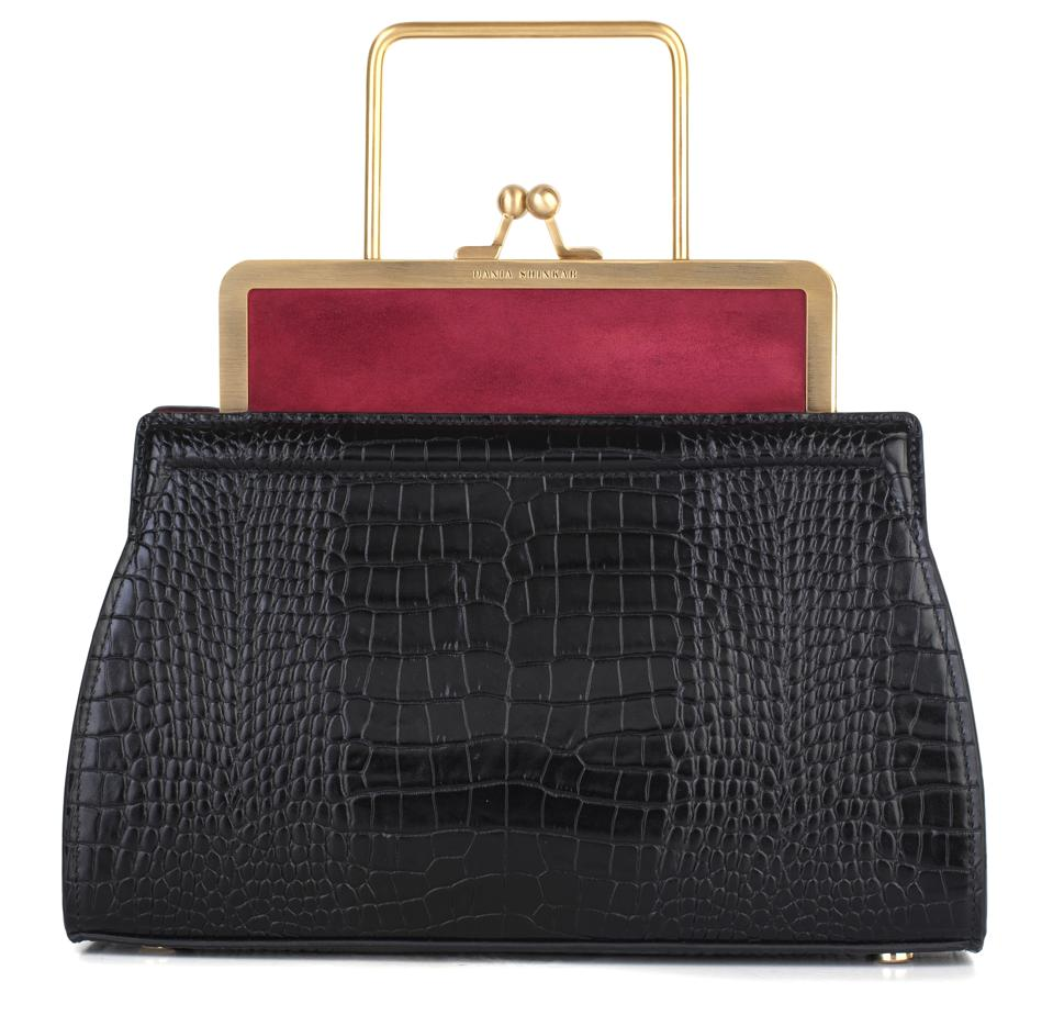 The DANA - Ruby/ Black, crafted from croc embossed calfskin and kidskin goat suede, is a vintage-inspired clasp bag featuring a custom brass frame with a fixed top handle. Kiss-lock frame closure, light gold-tone hardware, 100% made in Italy.