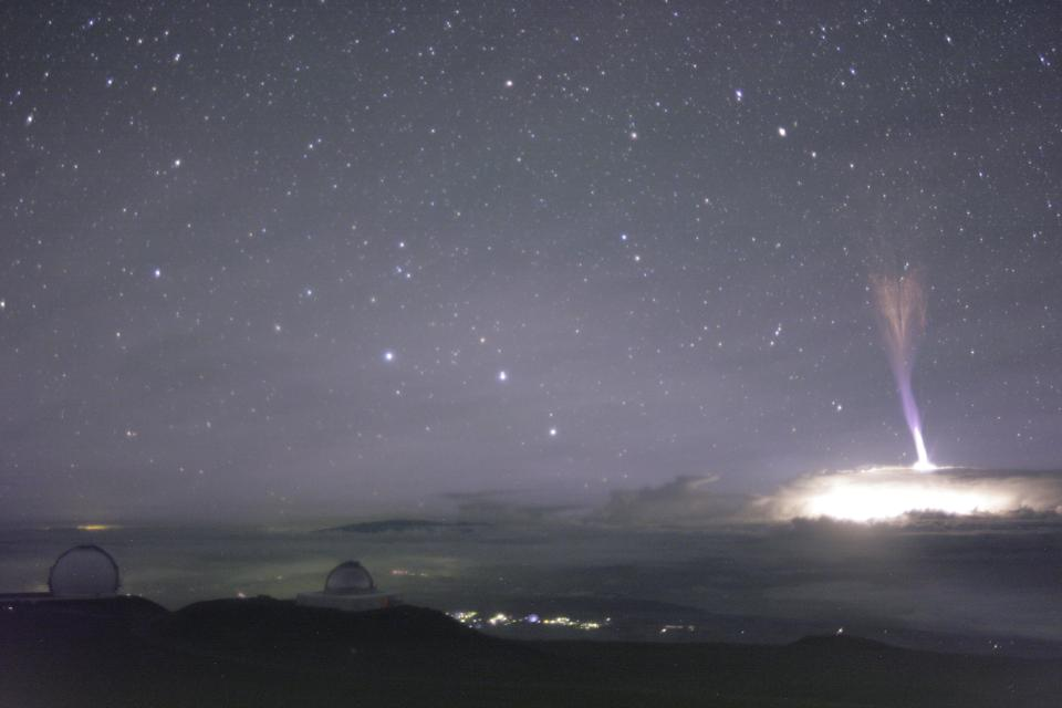 This photograph was taken at the summit of Mauna Kea, and depicts a blue jet nearby.