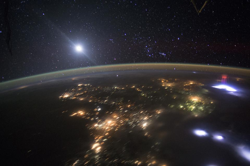 The ISS captures a red sprite occurring over a big thunderstorm's lightning strike.