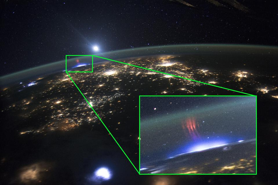 This photograph shows a red sprite appearing over a lightning strike at night, from space.