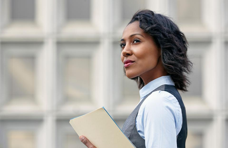 Portrait of young business woman holding paper work, looking away, side view