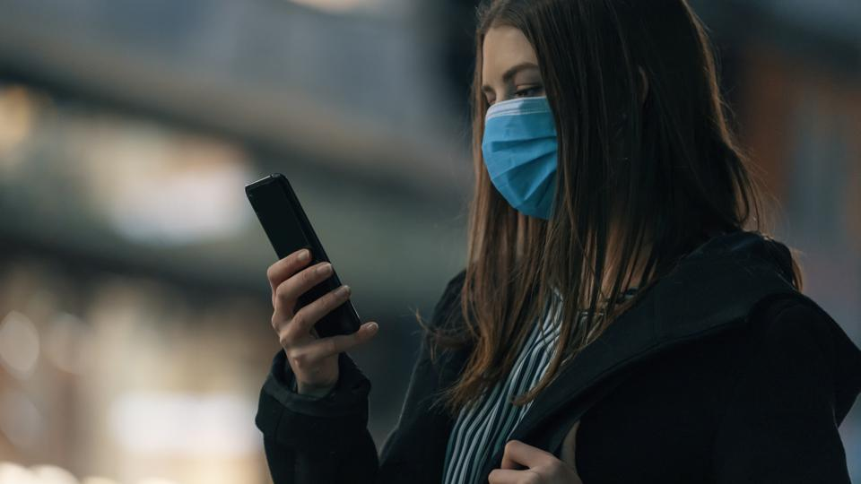 young girl using smartphone in city business district night with mask  during covid-19
