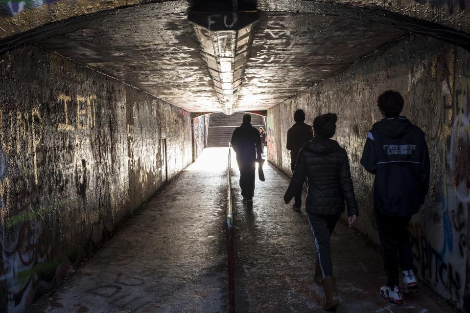 Students walk through paint covered tunnel