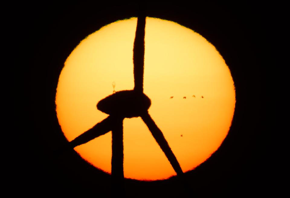 A silhouette of a wind turbine against the sun in the Hanover region of Germany.