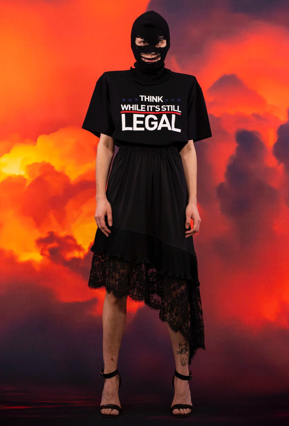 A model wearing a ski mask, asymmetrical black skirt and T-shirt that reads ″Think While It's Still Legal″.