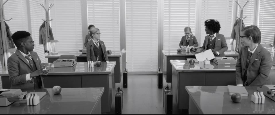 A black and white film still of kids dressed n suits playing at 'office.″