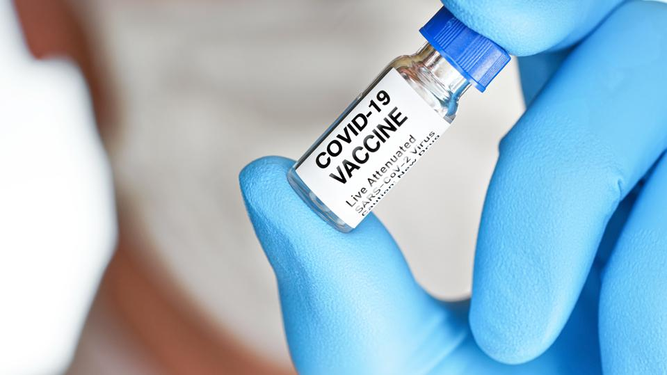Hand in blue medical gloves holding small vial with label Covid 19 vaccine (sticker is own design, not real product), blurred face covered with cotton mask background. Coronavirus cure concept