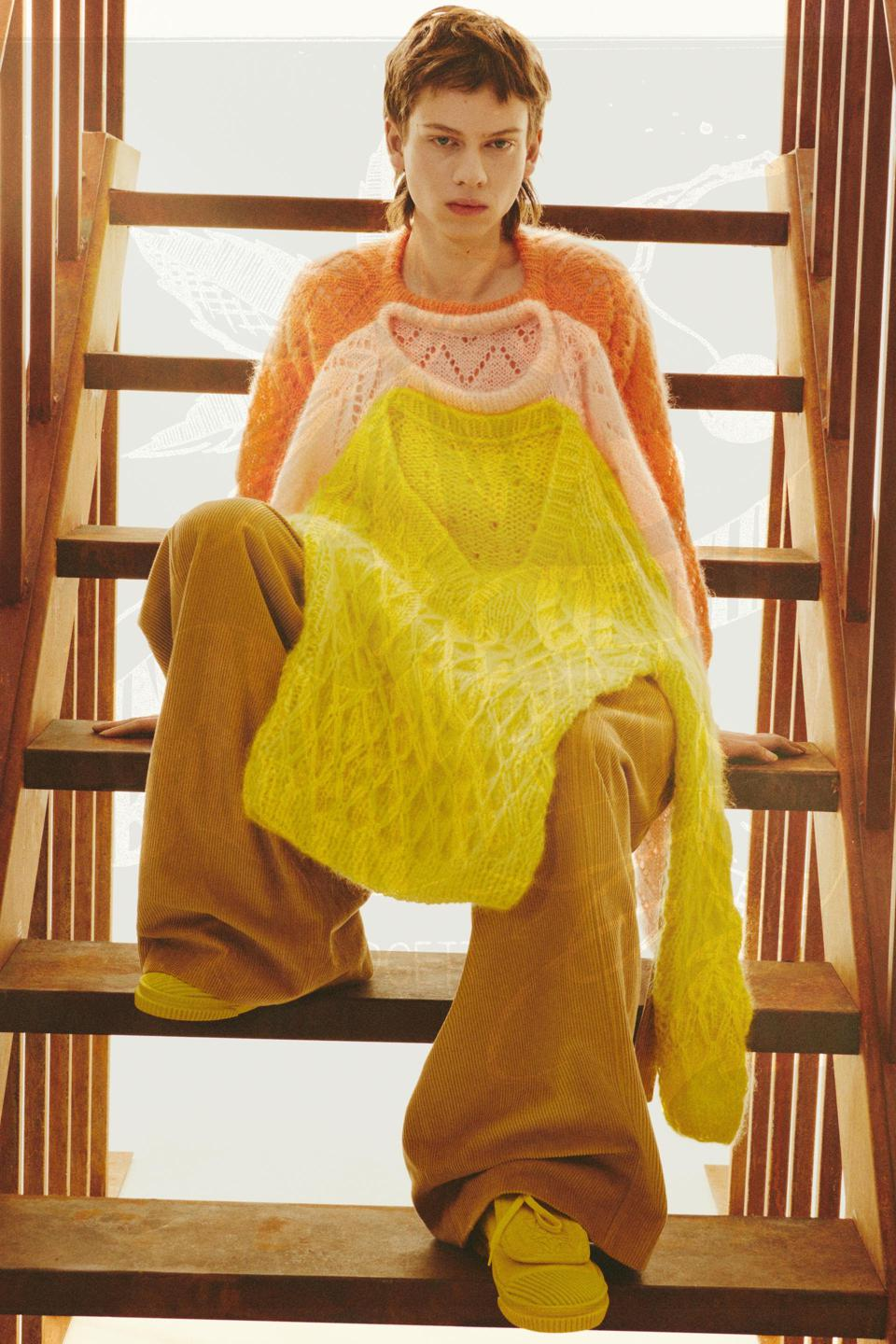 A models sits on a staircase wearing a sweater made from multiple sweaters