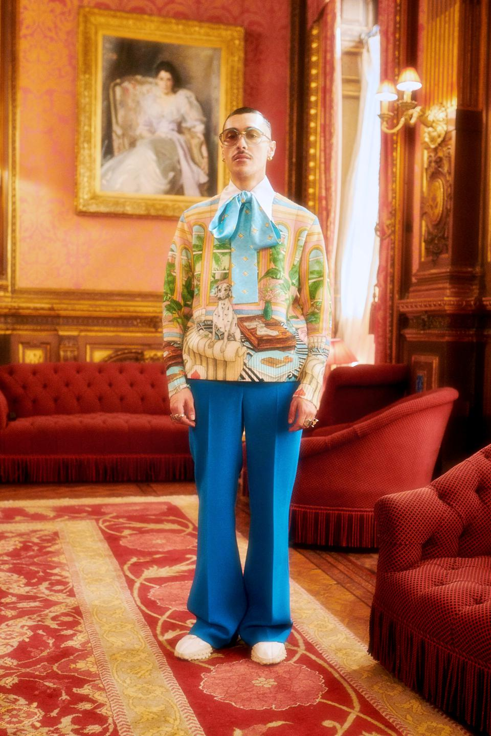 A male model wearing a colorful sweater with a bow and blue pants from the Casablanca ″Grand Prix.″collection.