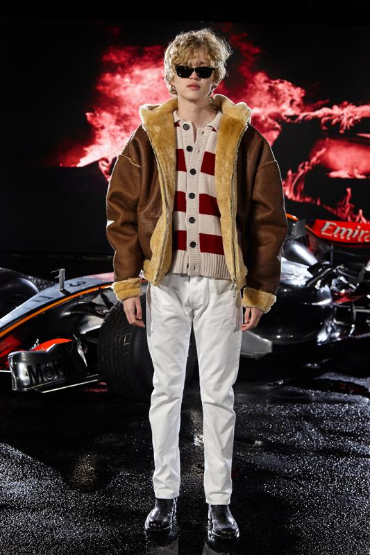 A model stands in front of a McLaren car modeling the Fall Winter 2021 men's collection