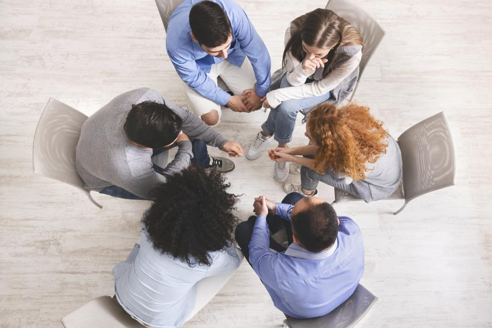 Group of people sitting in circle, dicussing problems during therapy session