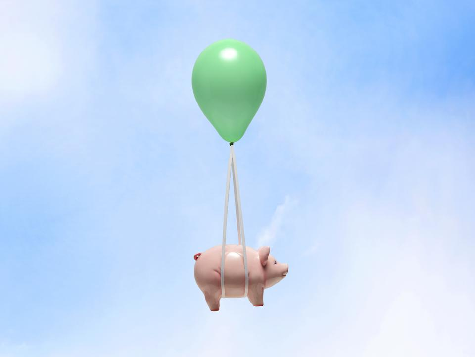 Piggy bank being carried by balloon