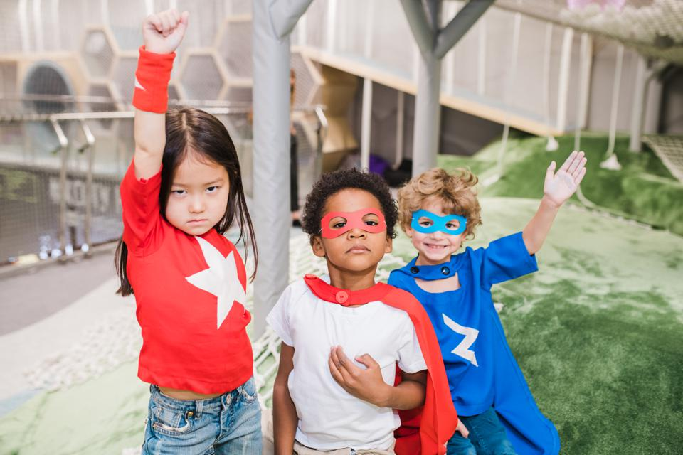Group of intercultural children in attire of superheroes playing together
