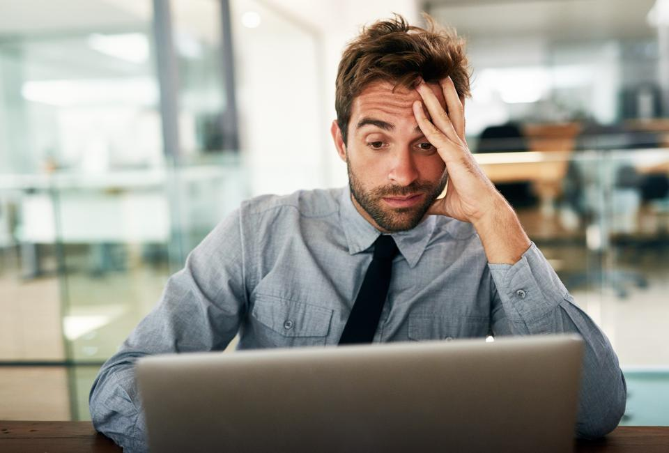 Shot of a businessman looking stressed while working at his desk in an office