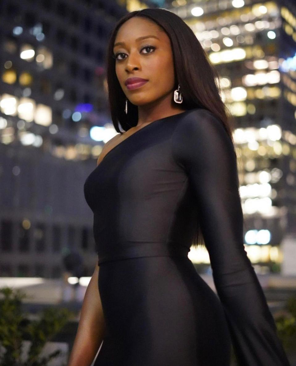 Chinenye ″Chiney″ Ogwumike stands in front of city buildings.