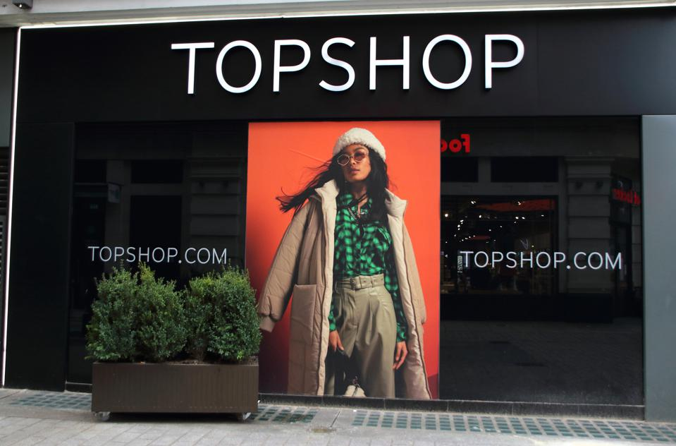 A Topshop ad featuring a model in a green checked shirt and khaki-colored pants in the window of a shuttered store in London.