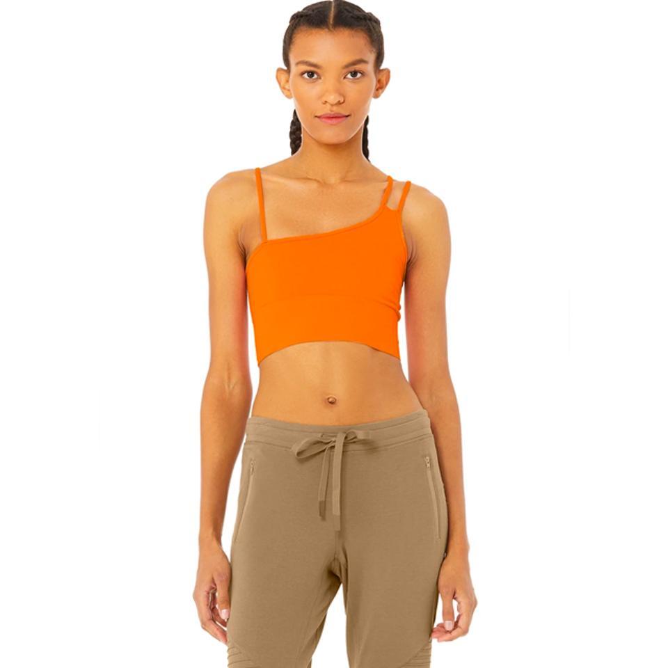 Model wearing orange asymmetric cut crop tank top