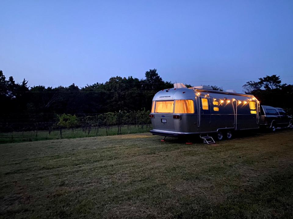 A silver Airstream trailer sits on the edge of a vineyard at night