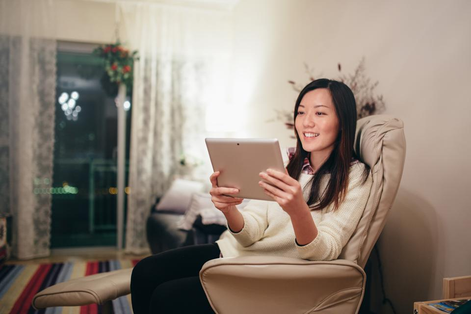 Woman relaxing on armchair with digital tablet