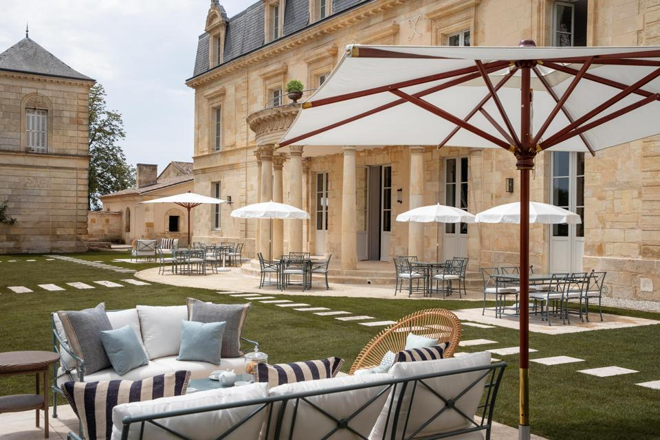 A French chateau fronted by a grassy terrace with tables and chairs