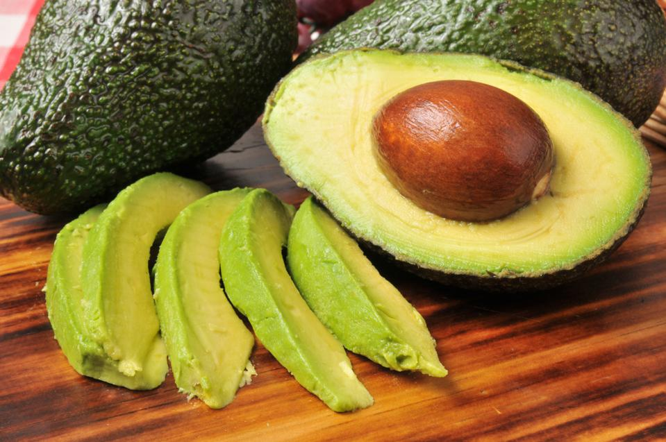 Whole avocados, a sliced half avocado with the pit still in and slices of avocado are displayed on a cutting board in this photo by Getty Creative