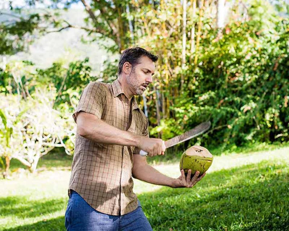 Co-founder of Mana Artisan Botanics, Steve Sakala, opens a coconut on his farm Honaunau Farm.