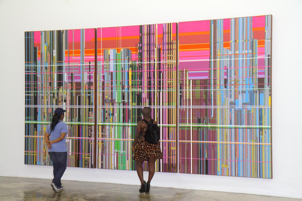 Two women looking at a painting of the Rubell Family Collection.