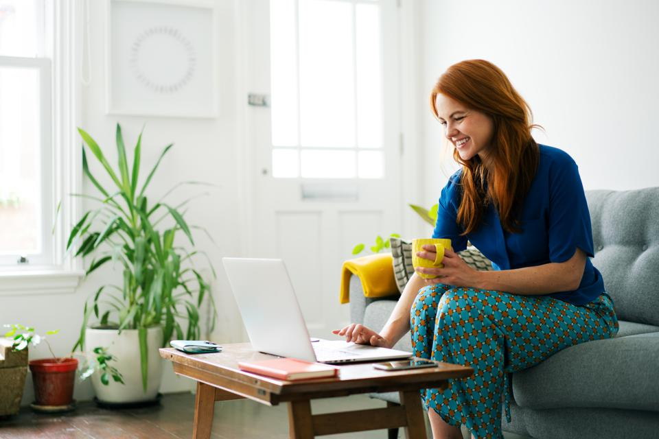 Woman using laptop from sofa, smiling
