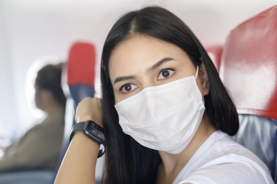 Traveling woman wearing protective mask onboard in the aircraft using smart watch, travel under Covid-19 pandemic, safety travels, social distancing protocol, New normal travel concept