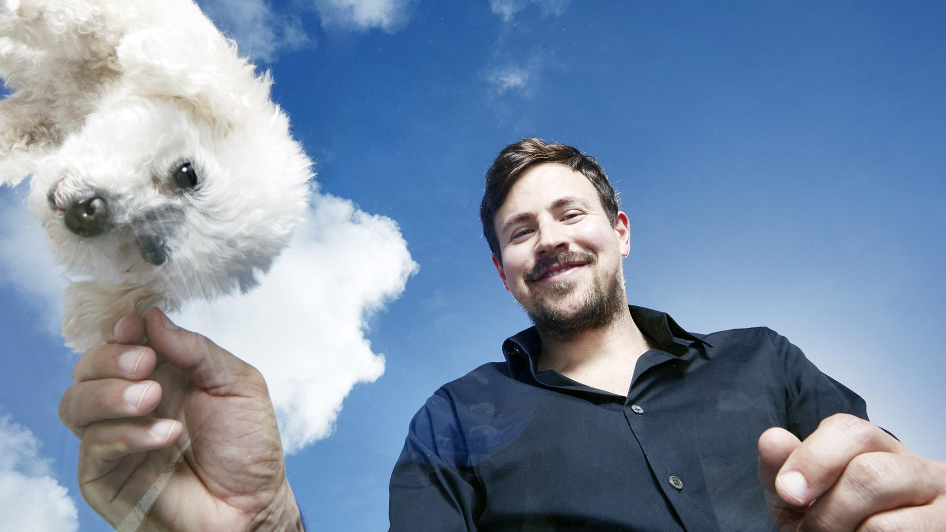Ryan Cohen plays with furry white dog. He's the Founder and former CEO of Chewy.