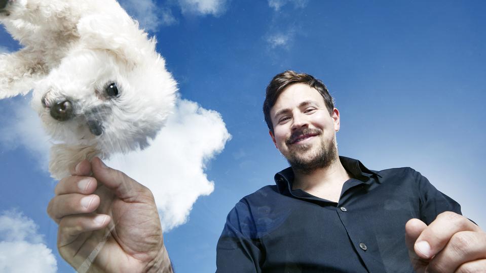 Рајан Коен си игра со крзнено бело куче. Тој е основач и поранешен извршен директор на Chewy.
