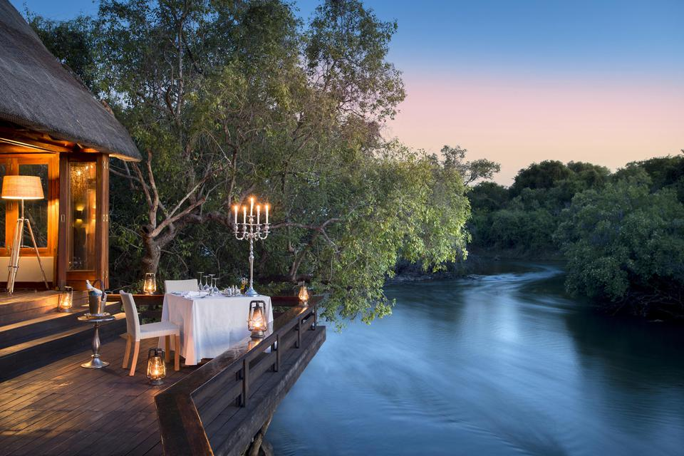 A table at twilight with lighted candles on the banks of the Zambezi River