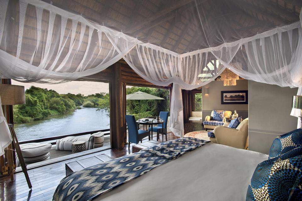 A four poster bed draped with mosquito netting looking out at the Zambezi River