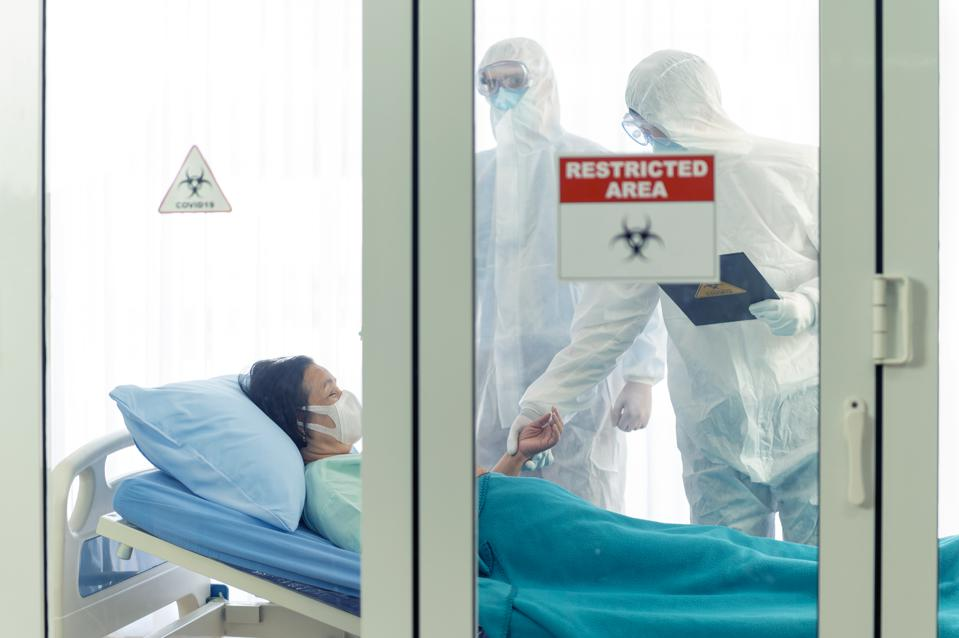 Doctors wearing PPE examine Covid-19 patient in a restricted clean room area.