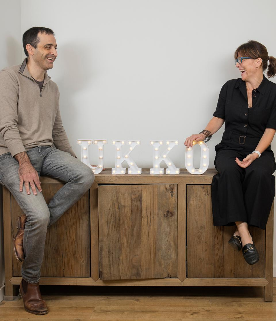 One white man and one white woman sitting on a wooden credenza laughing at each other.