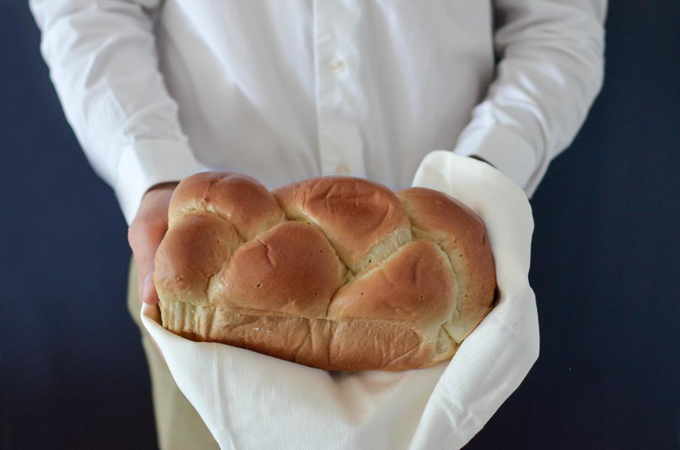 A person dressed in a white button up shirt holding out a loaf of braided bread. No face is visible.
