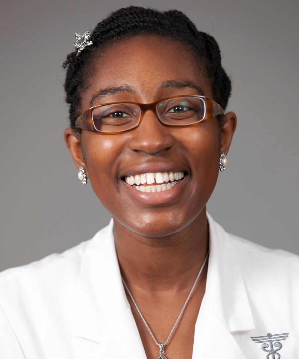 A Black woman in glasses and a white lab coat looking into the camera smiling