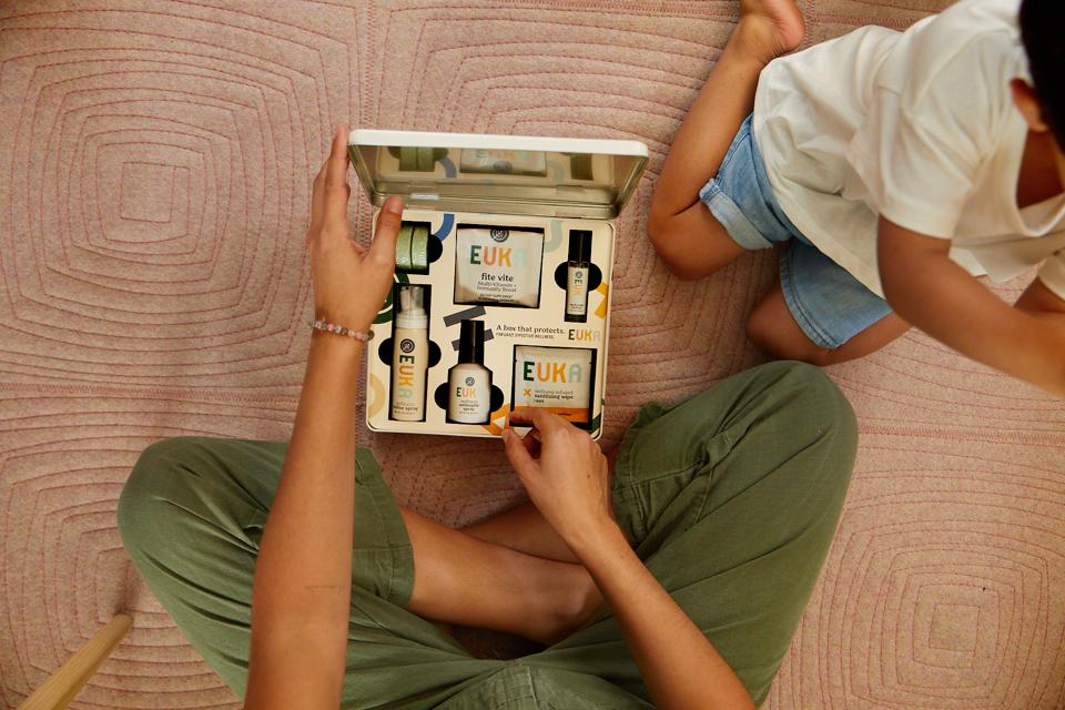 A woman opens a box of Euka products next to a little boy.