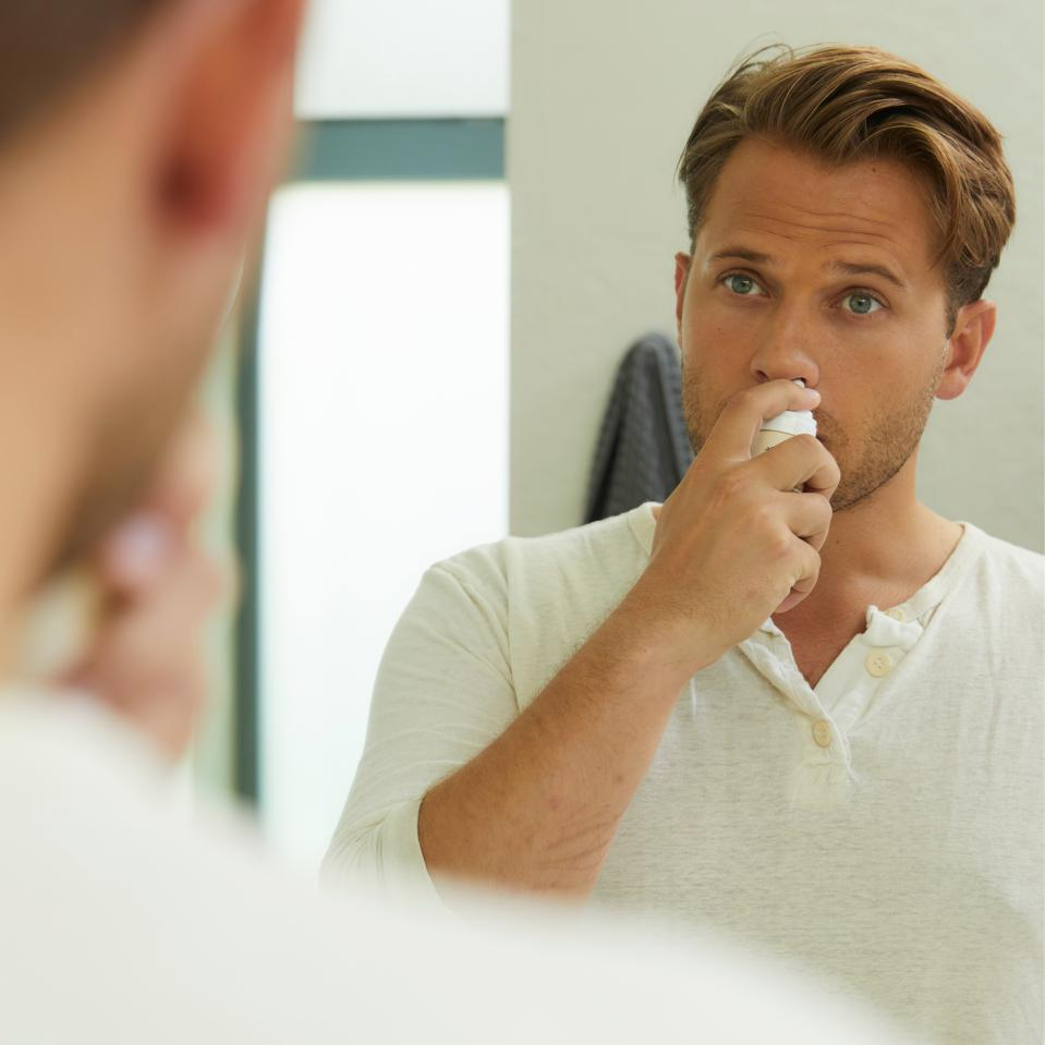 A white man with blonde hair uses a nasal spray while looking in the mirror.