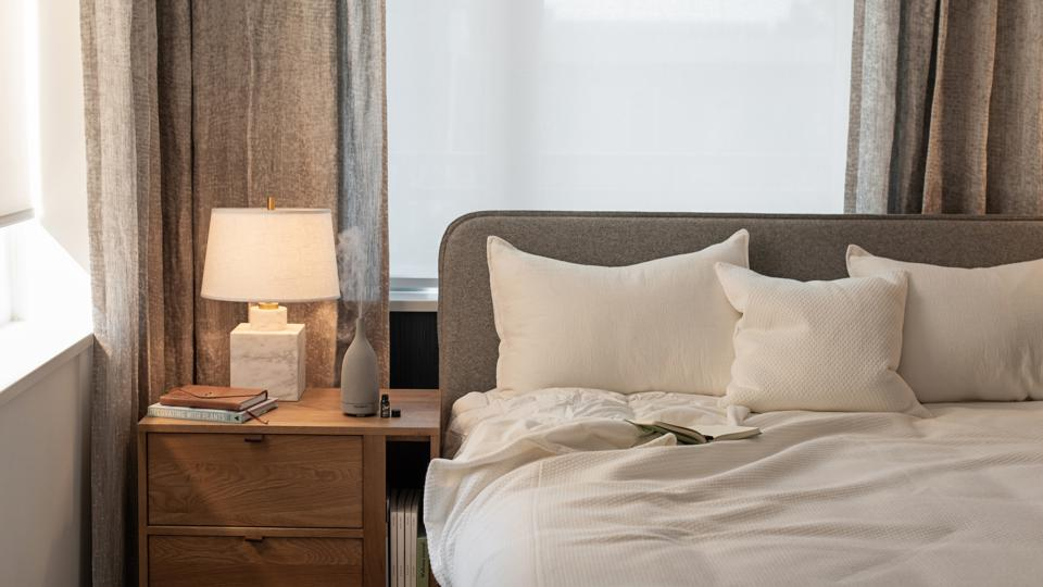 An essential oil diffuser on a wood bedside table next to a bed with white bedding.