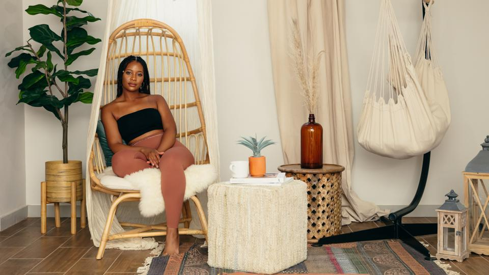 Black girls breathing founder Jasmine Marie sits in a wooden chair in a brightly-lit room