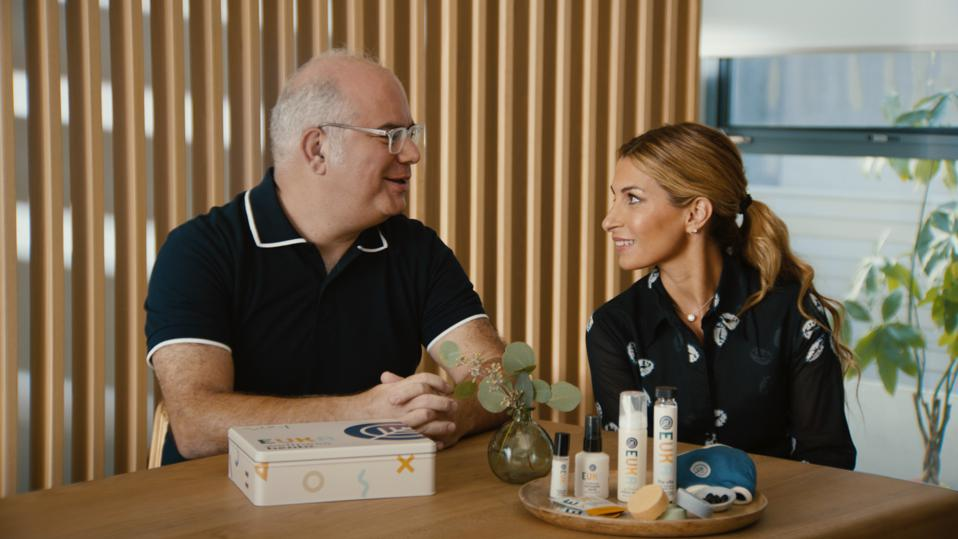 Dr. Shawn Nasseri and his partner Dr. Bita Nasseri sit at a wood table with Euka products