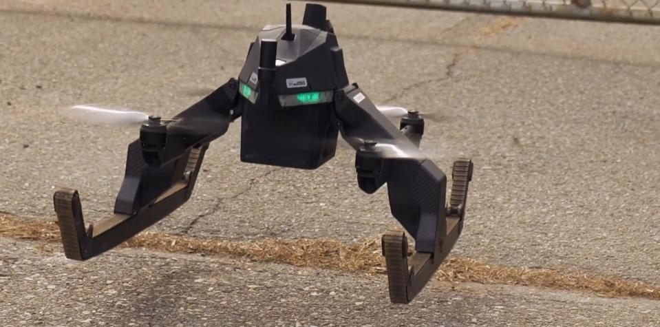 A hybrid air/ground drone lifts off from ground using four small rotors.