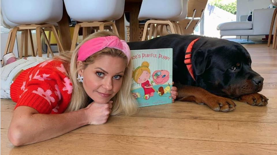 Candace Cameron Bure taking a photo with her dog and her new book