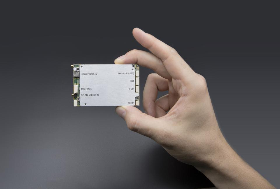 A hand holds an embedded module smart radio the size of a pack of playing cards.