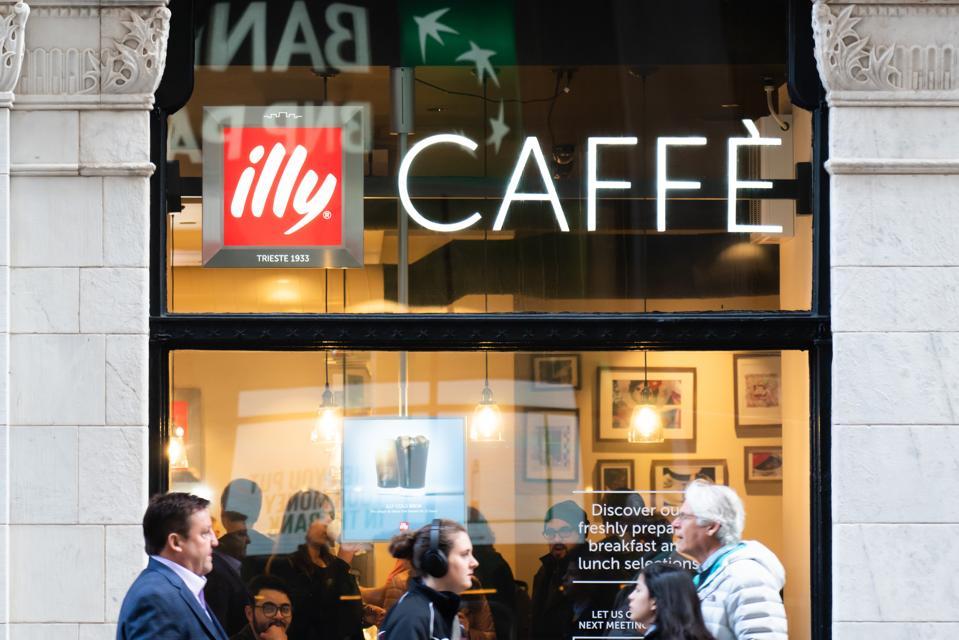 Pedestrians walk past an Illy Caffe...